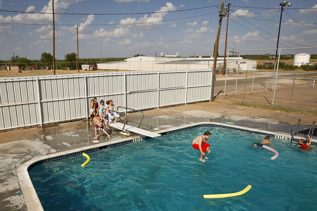 Caleb Ward, 10, does a cannonball as children play in the Robert Lee city pool as the temperature toped out at 110 degrees, Wednesday, Aug. 10, 2011, in Robert Lee.  The city's pool was recently used by a firefighting helicopter when it scooped several hundred gallons to be dropped on a nearby wildfire that threatened the town and burnt 160,000 acres. Photo: Michael Paulsen/Houston Chronicle