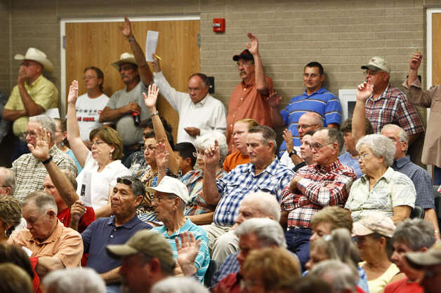 Robert Lee residents raise their hands when asked if they would be interested in volunteering their time and resources to build a pipeline to nearby town Bronte which would ship water the to the drought stricken town during a town hall meeting attraction nearly 300 residents, Wednesday, Aug. 10, 2011, in Robert Lee. Photo: Michael Paulsen/Houston Chronicle