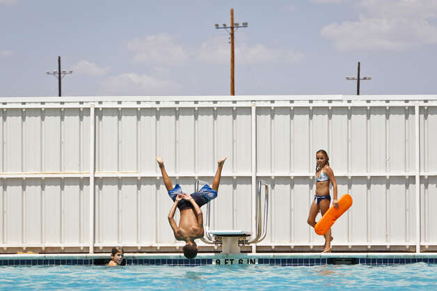 Trace Oleksiuk, 12, jumps into the Robert Lee city pool as the temperature toped out at 110 degrees, Wednesday, Aug. 10, 2011, in Robert Lee.  The city's pool was recently used by a firefighting helicopter when it scooped several hundred gallons to be dropped on a nearby wildfire that threatened the town and burnt 160,000 acres. Photo: Michael Paulsen/Houston Chronicle