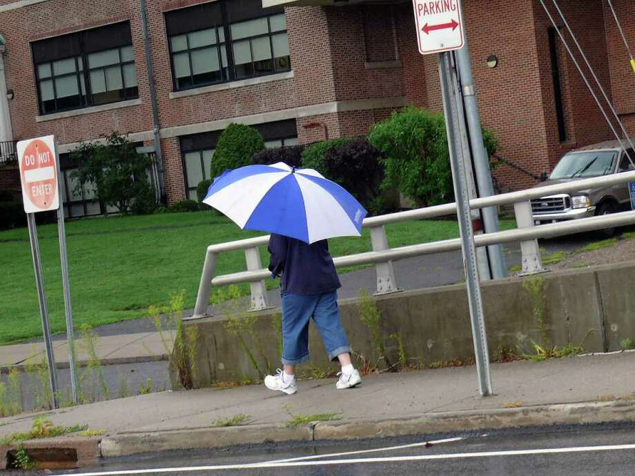 Umbrellas were a necessary accessory Monday as the rainy weather that started Sunday continued into the work week. Photo: Genevieve Reilly / Fairfield Citizen