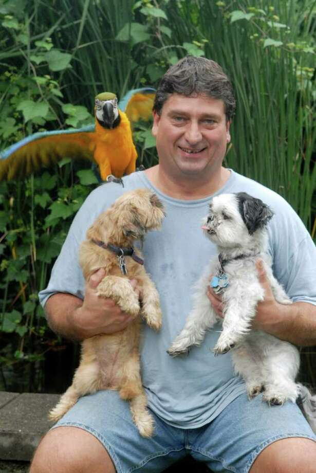 "Jeff Manka at his home on Wallace St. in the Shippan section of Stamford, Conn. on Monday August 15, 2011 with his Macaw ""Magoo"" and two of his 5 dogs Shih Tzus ""Angel"" and ""Magoo"". Photo: Dru Nadler / Stamford Advocate Freelance"