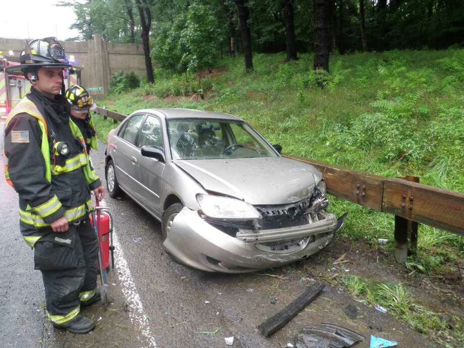 A firefighter surveys damage to one of two cars that collided Monday morning on the Merritt Parkway in Westport, sending its driver to the hospital. Photo: Westport Fire Department / Westport News contributed