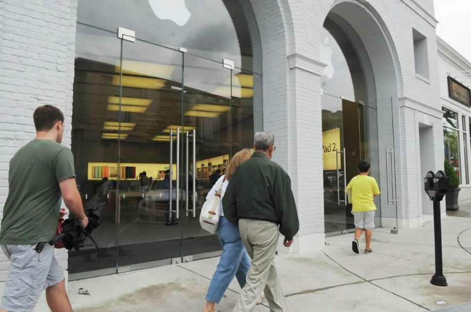 """Pedestrains walk past the glass exterior of Apple Store on Monday, Aug. 15, 2011. Controversy surrounds Apple's planned installation of what some are calling an """"unsightly"""" security gate at the electronics retailer's Greenwich Avenue store. Photo: Helen Neafsey / Greenwich Time"""
