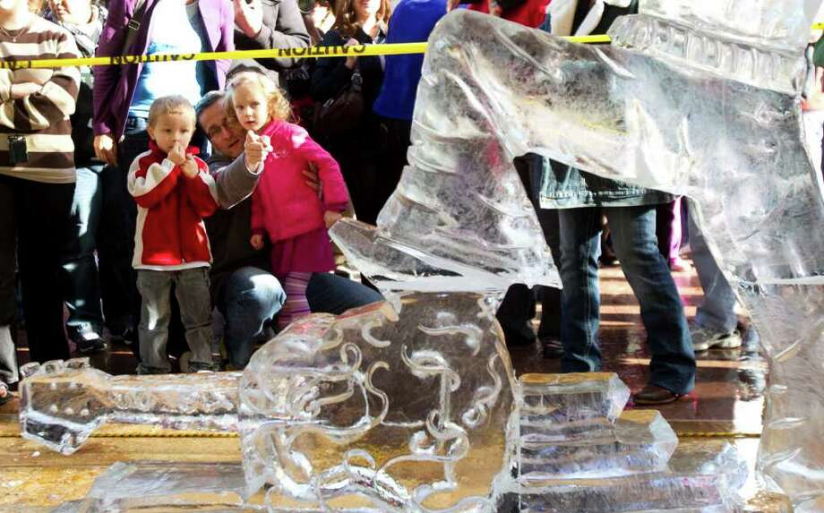 Carsten Hentschel and his children Hannes, left, and Gesa, right,  looks at an Elvis sculpture by Marco Villarreal, of Las Vegas, during the 3rd Annual Magnificent Seven All Out Ice Sculpting Competition at Discovery Green Saturday, Jan. 8, 2011, in Houston. Photo: Brett Coomer, Houston Chronicle / Houston Chronicle