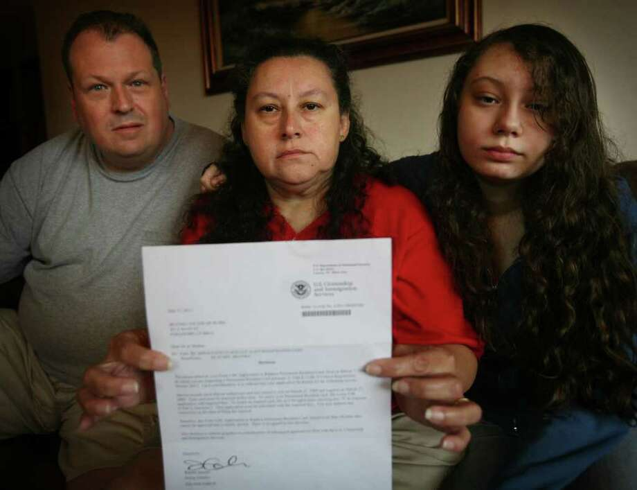 Flanked by her husband Al and daughter Allie, 14, Beatriz DeRubis of Stratford shows the letter that she received from immigration denying the renewal of her Green Card. Photo: Brian A. Pounds / Connecticut Post