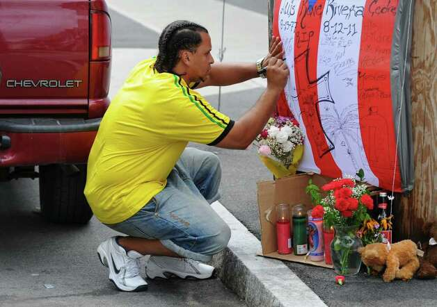 Rick Clark signs a flag at a street memorial for Luis Rivera, who was shot and killed by police on Friday, at Grove Place on Sunday Aug. 14, 2011 in Schenectady, NY.   (Philip Kamrass / Times Union) Photo: Philip Kamrass / 00014274A