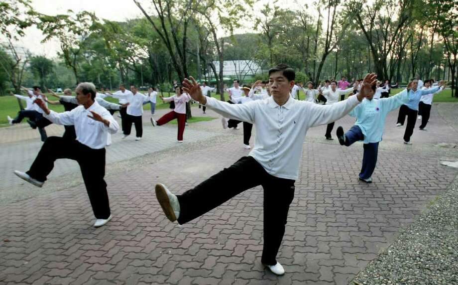 FILE - In this Jan.18, 2011 file photo Thai-Chinese men and women take morning exercise by practicing Chinese martial arts at a park in Bangkok, Thailand.  New research concludes that even 15 minutes of moderate exercise like brisk walking can add years to your life. (AP Photo/Apichart Weerawong, File) Photo: Apichart Weerawong