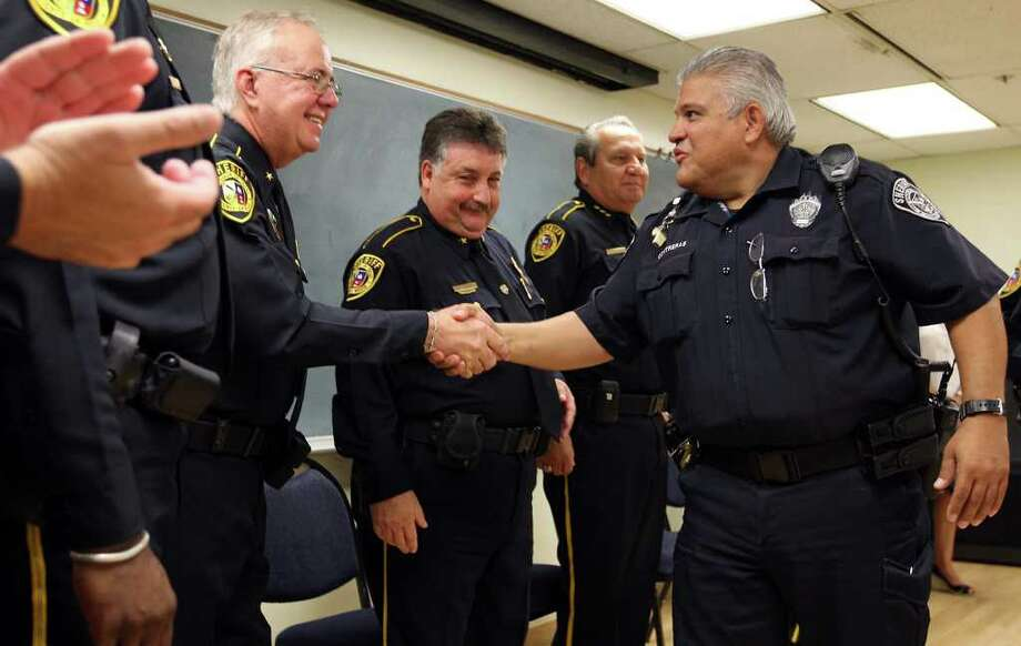 Bexar County Sheriff Deputy of the Year Larry Contreras, right, is congratulated by the department's top brass including from left, Deputy Chief Charles Benson, Deputy Chief Ray Lujan and Chief Deputy Manuel Longoria, Monday, Aug. 15, 2011. Contreras was honored with a ring for actions he took while off-duty on May 2010. He confronted a man with who fired a shotgun while cruising near the deputy's house. The deputy held suspect until San Antonio police arrived. Photo: JERRY LARA, Jerry Lara/Express-News / SAN ANTONIO EXPRESS-NEWS