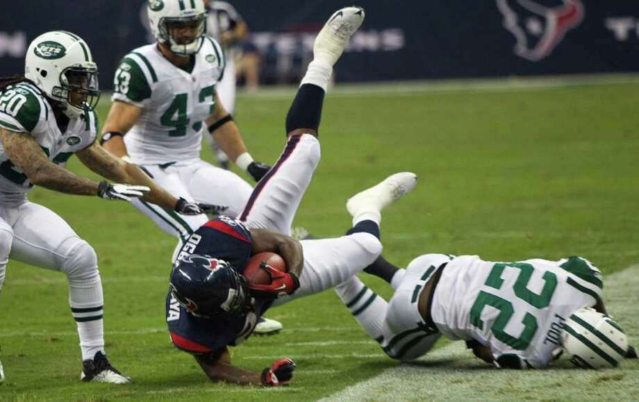 Houston Texans running back Chris Ogbonnaya (27) is tripped up by New York Jets safety Brodney Pool (22) after a reception during the first half of an NFL football game at Reliant Stadium Monday, Aug. 15, 2011, in Houston.  ( Brett Coomer / Houston Chronicle ) Photo: Brett Coomer, Staff / © 2010 Houston Chronicle