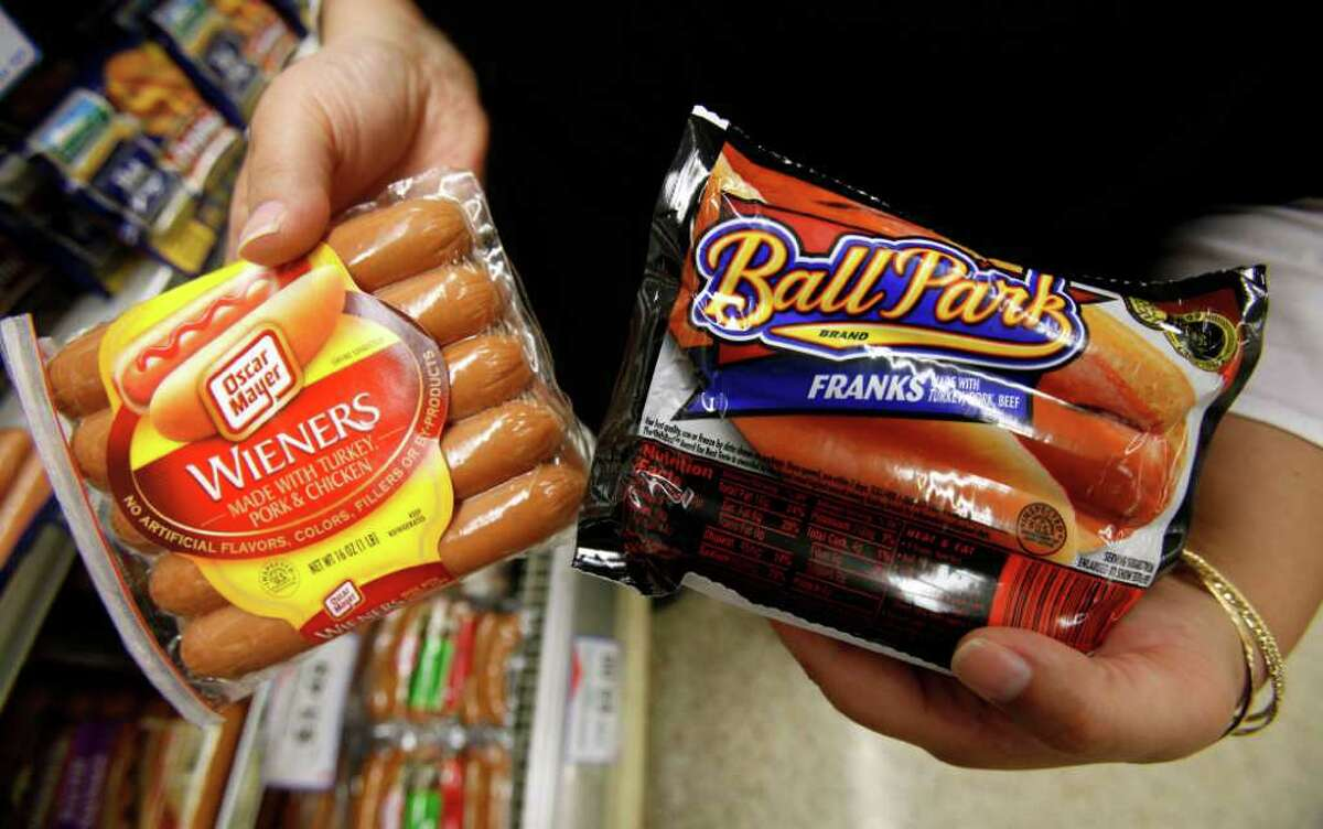 FILE - In this May 22, 2009 file photo, a store employee holds packages Oscar Meyer wieners, a Kraft product, left, and Ball Park franks, a Sara Lee Corp. product, at a local Dahl's grocery store in Des Moines, Iowa. The nation?s two largest hot dog makers are taking their legal beefs to federal court in Chicago, where a judge will determine whether either broke false-advertising laws when boasting about their top-dog status. (AP Photo/Charlie Neibergall, File)