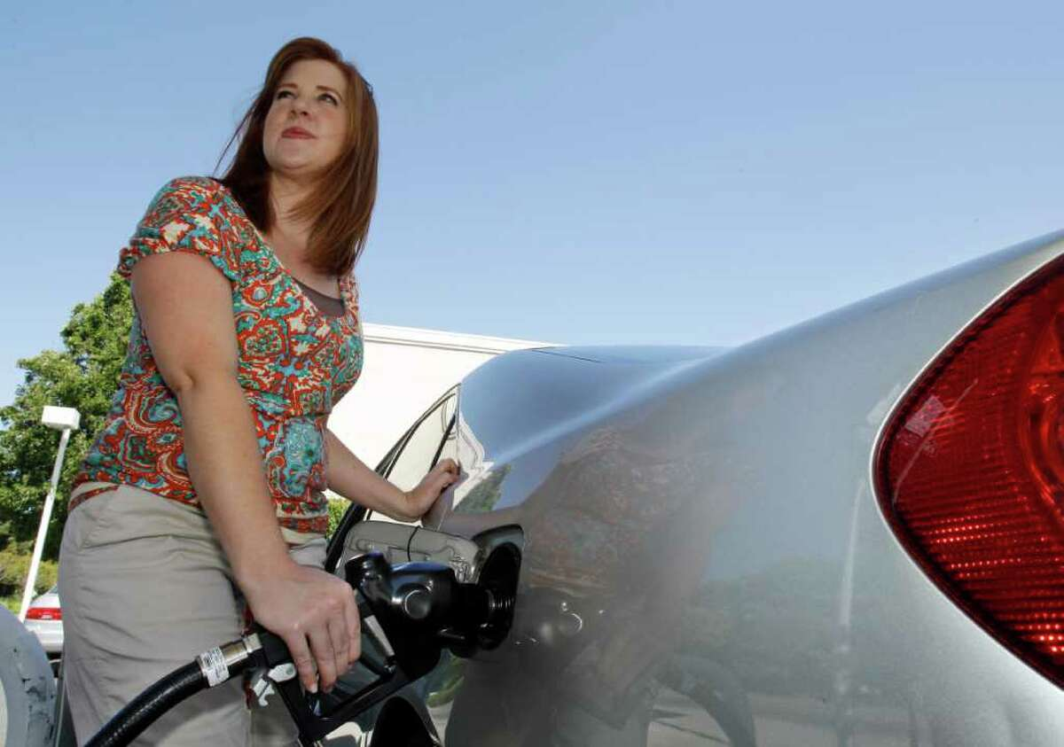 In this June 21, 2011 photo, Shell gas customer Carissa Wiley, of Fresno, Calif., pumps gas at a Shell gas station in Menlo Park, Calif. Oil jumped to the highest level in more than a week Monday, Aug. 15, 2011, alongside a broad rally on Wall Street and a report that Japan's economy contracted less than expected last quarter. (AP Photo/Paul Sakuma)