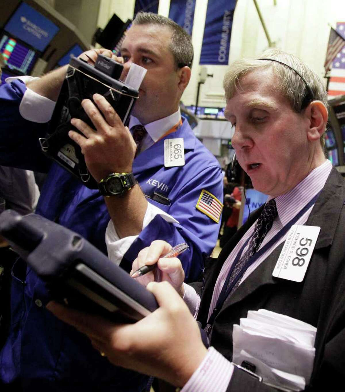 Richard Cohen, right, works with a fellow trader on the floor of the New York Stock Exchange Monday, Aug. 15, 2011. (AP Photo/Richard Drew)