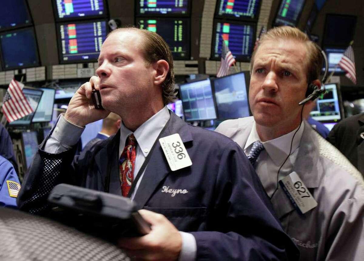 Traders Andrew Igoe, left, and Michael Smyth work near the post that trades Motorola Mobility on the floor of the New York Stock Exchange Monday, Aug. 15, 2011. (AP Photo/Richard Drew)