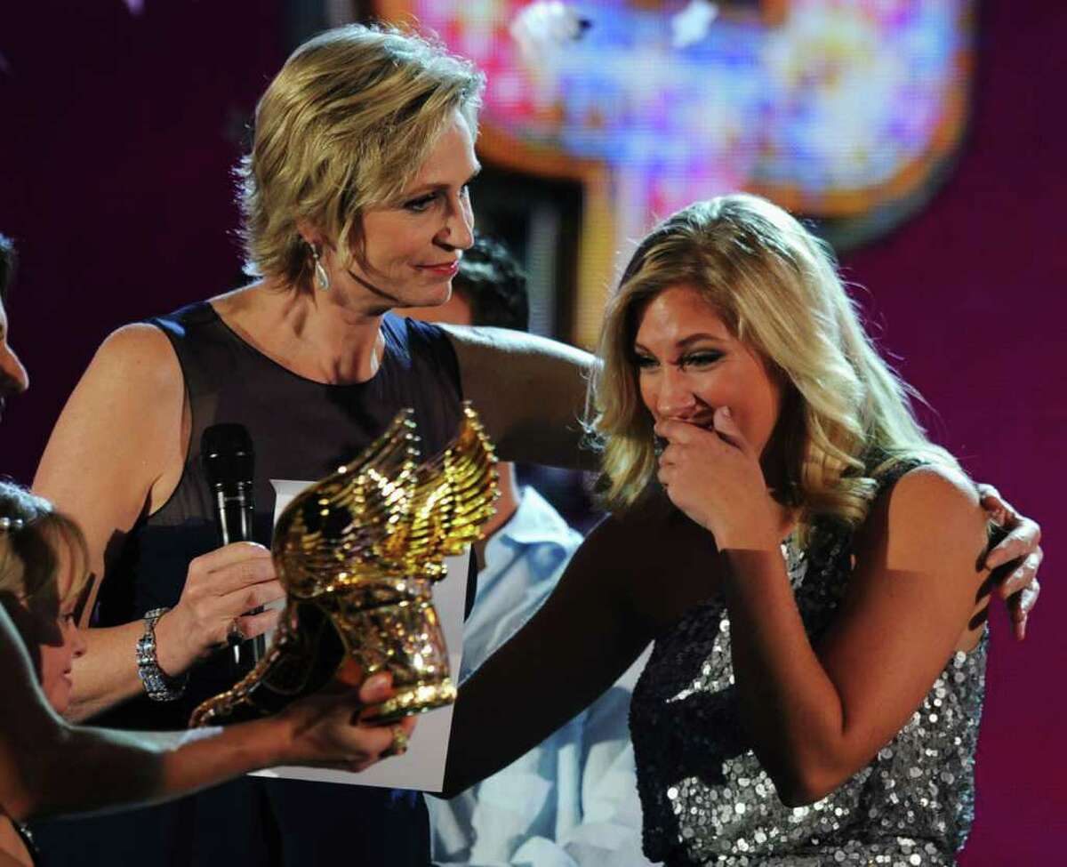 Host Jane Lynch presents the Crown Do Something 100K Winner award to Sarah Cronk onstage during the 2011 VH1 Do Something Awards at the Hollywood Palladium in Hollywood, California.