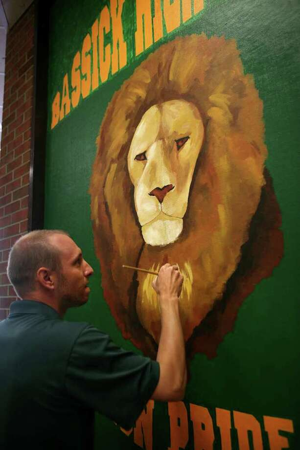 Art teacher Brian Schmitt of Shelton paints a lion mural in the entryway at Bassick High School in Bridgeport on Tuesday, August 16, 2011. Photo: Brian A. Pounds / Connecticut Post