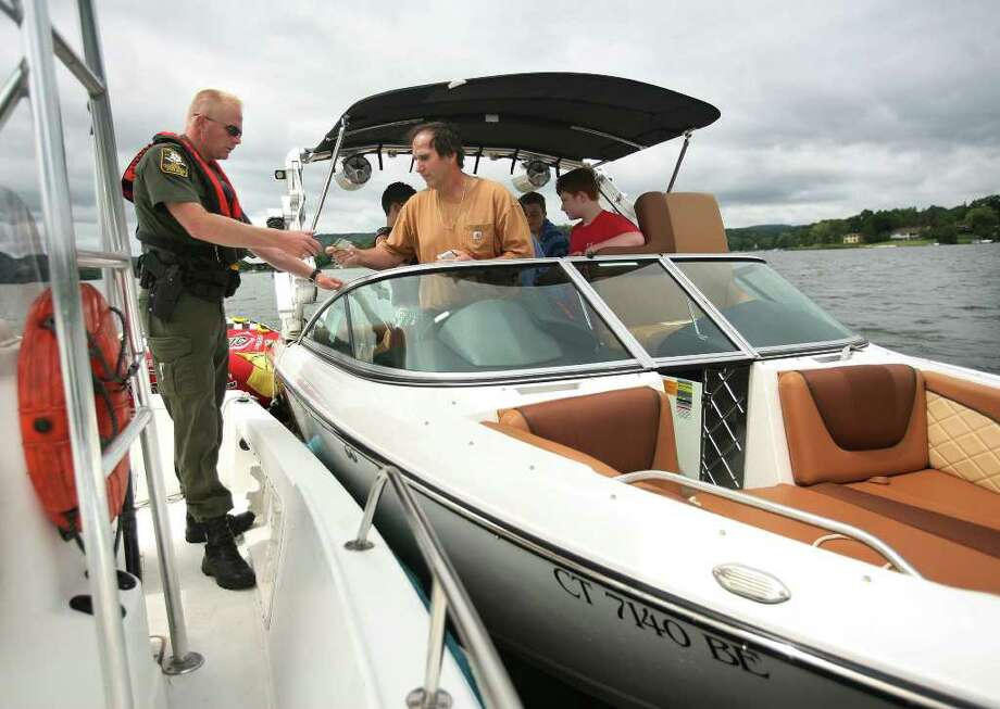 State Environmental Conservation Police Officer Keith Williams, left, checks a boater's license during a patrol of Candlewood Lake in Brookfield on Tuesday, August 16, 2011. Photo: Brian A. Pounds / Connecticut Post