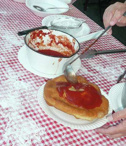 Tomato sauce is ladled onto each pizza fritta, followed by a sprinkling of Parmesan cheese. Photo: Anne W. Semmes