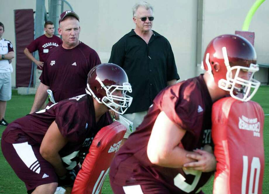 Texas A&M offensive line coach Jim Turner, left, and coach Mike Sherman watch the offensive line practice during the NCAA college football team's workout Tuesday, Aug. 9, 2011, in College Station, Texas. (AP Photo/Bryan College Station Eagle, Stuart Villanueva) Photo: Stuart Villanueva, MBR / Bryan College Station Eagle