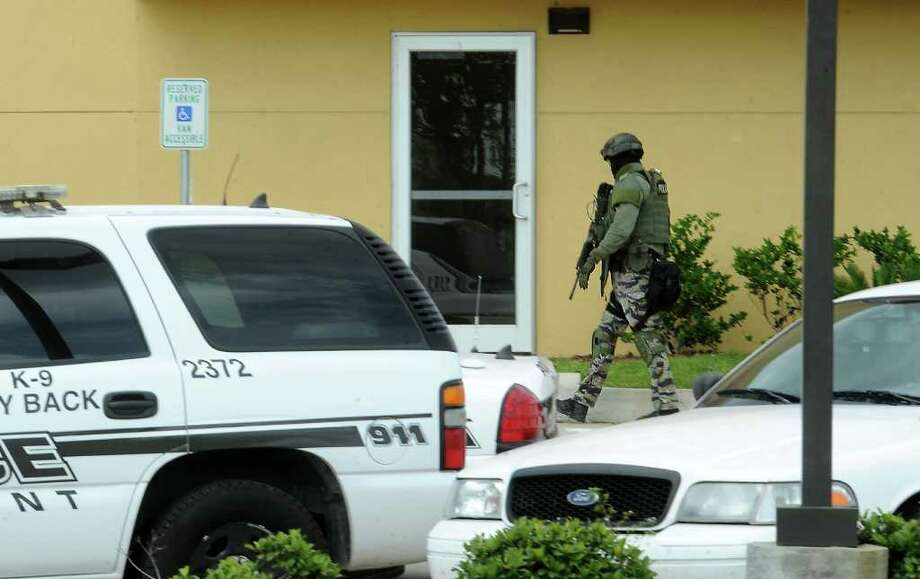 The beaumont police department moves in during a stand off at Red Roof Inn in Beaumont, Saturday. Tammy McKinley/The Enterprise Photo: TAMMY MCKINLEY