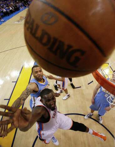 Oklahoma City Thunder center Kendrick Perkins, front, and Denver Nuggets forward Kenyon Martin reach for a rebound in the third quarter of Game 2 of a first-round NBA basketball playoff series in Oklahoma City, Wednesday, April 20, 2011. Oklahoma City won 106-89. (AP Photo/Sue Ogrocki) Photo: Sue Ogrocki, STF / AP