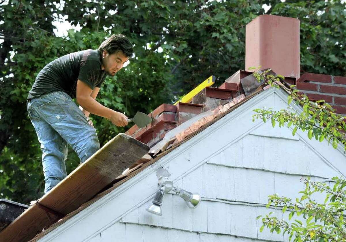 Johnny Arce, a subcontractor, completes work on a new chimney at the Richter House in Danbury Tuesday. Photo taken Tuesday, August 16, 2011.