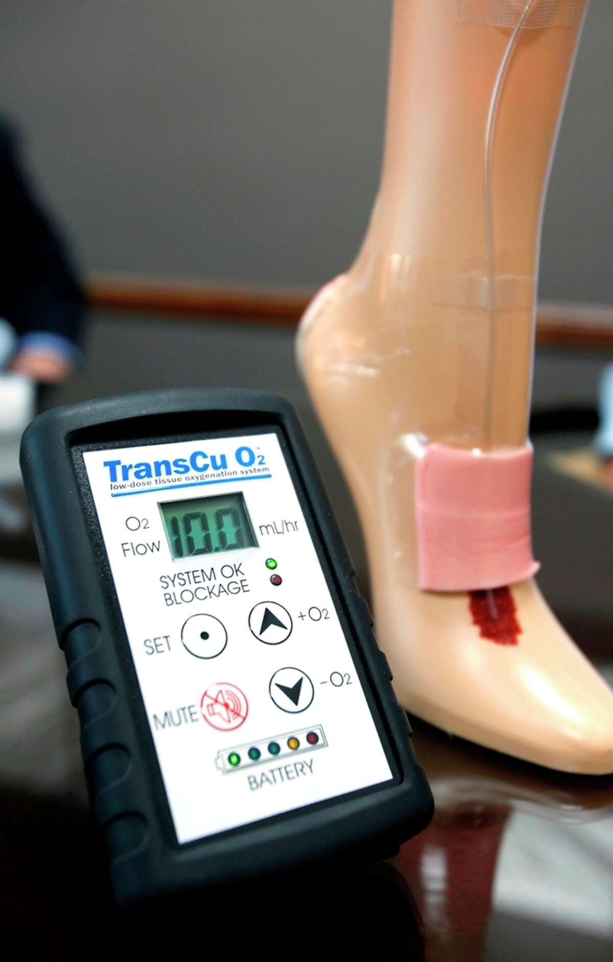 EO2 Concepts' TransCu O2 tissue oxygenation and would treatment system is seen in the company's San Antonio headquarters next to a foot showing a cut-away view of how the oxygenation system is applied to a wound.