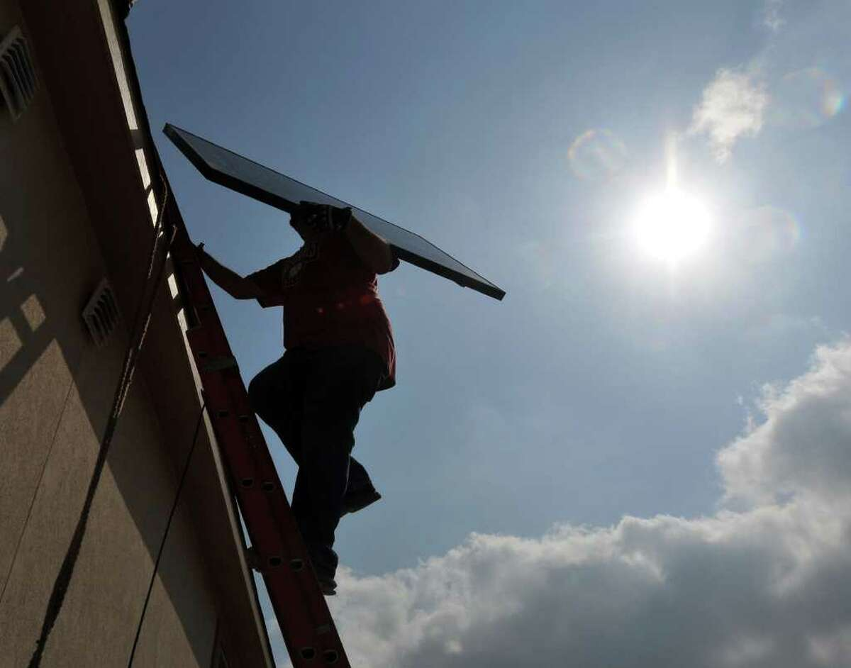 Jay Hicks of Solar Community Inc. carries a solar panel up a ladder to be installed on a roof of a home being built on the far North Side.