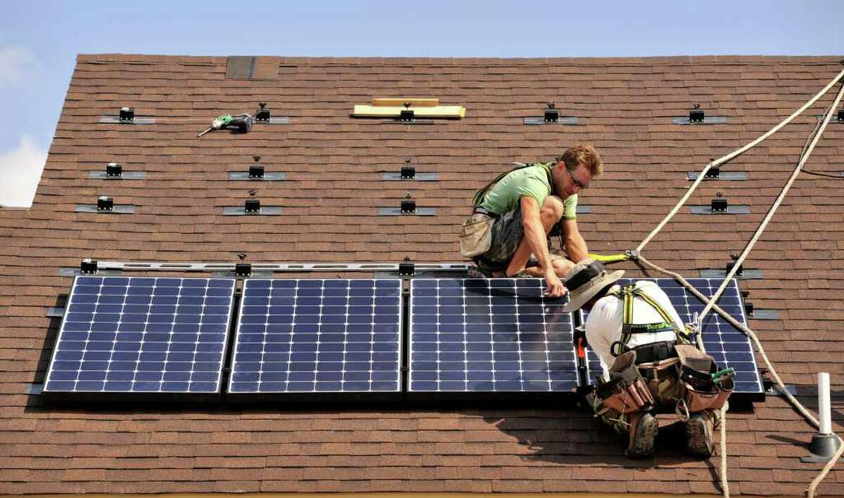 Jeff Swindle (top) and Travis Cucinello (bottom) both of Solar Community Inc., install solar panels on a home in the La Fontana neighborhood on the far North Side.