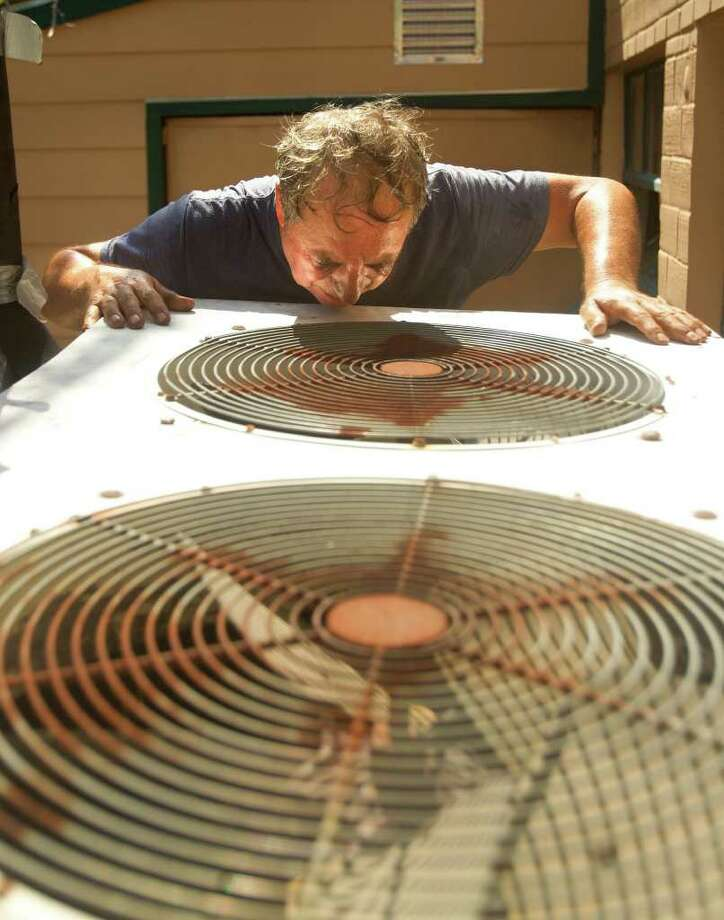 """Jose Juarez Sr., looks down into a water chiller after replacing a fan motor at Wolfe's Cleaners in mid-August. """"The fan went out after it got hot due to the extreme heat,"""" co-owner Jose Juarez Jr. said. Photo: Cody Duty, Staff / © 2011 Houston Chronicle"""