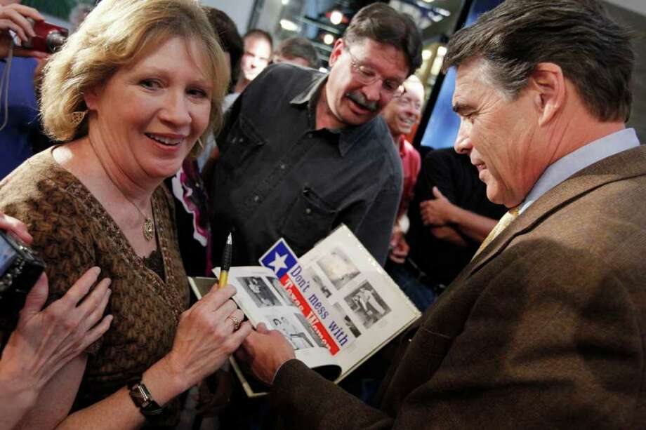 Becky Roe of Coal Valley, Iowa, left, shows Republican presidential candidate, Texas Gov. Rick Perry, a picture of himself as a high school sophomore in the 1966 Paint Creek School yearbook while he makes a campaign stop at the Iowa 80 Group truck stop in Walcott, Iowa, Tuesday, Aug. 16, 2011. Roe, who lived in Paint Creek, Texas, was a third grader when Perry was a high school sophomore. (AP Photo/Charles Dharapak) Photo: Charles Dharapak, STF / AP