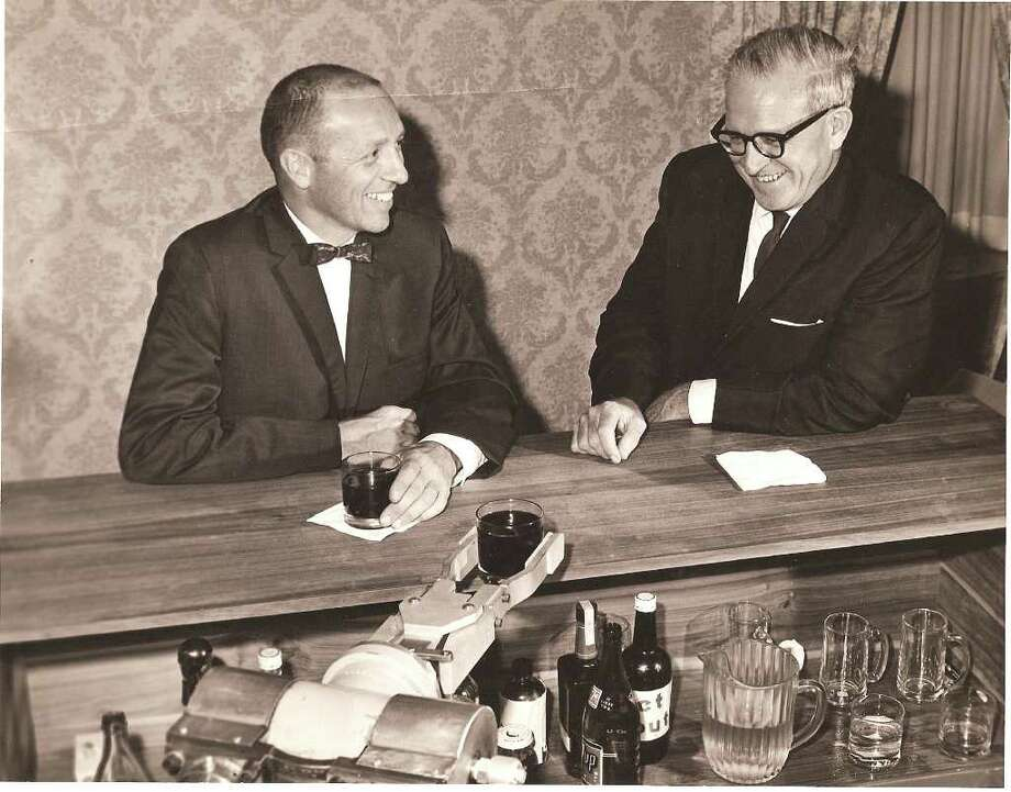 George C. Devol, right, and Joseph F. Engelberger are served by the Unimate mechanical arm that Devol invented and Engelberger's company produced. Devol, a former Greenwich resident, died Aug. 11 at his home in Wilton at age 99. Photo courtesy of the estate of George C. Devol Photo: Contributed Photo