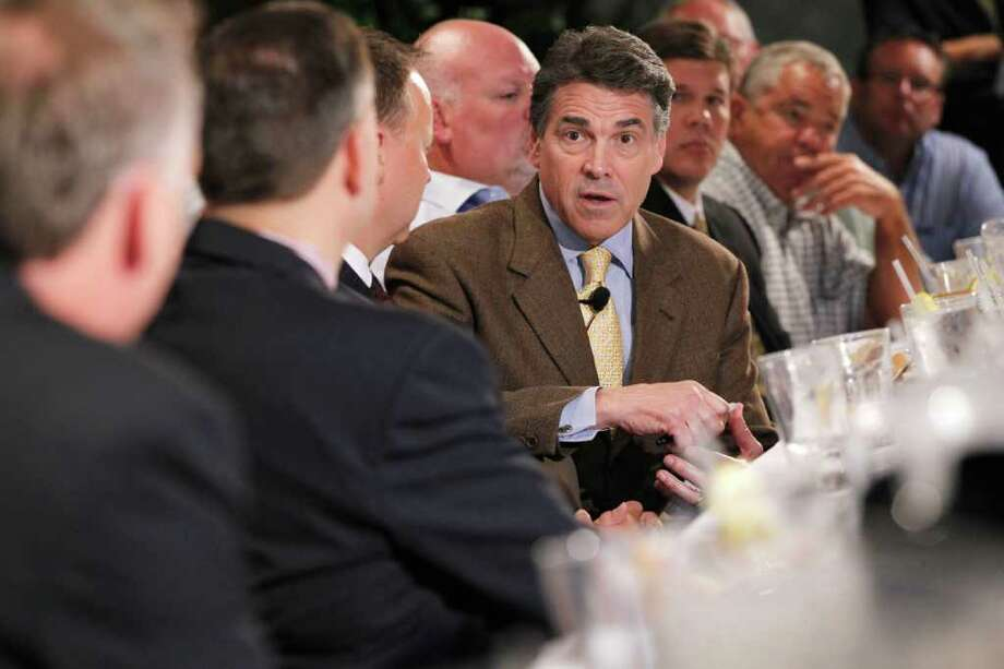Republican presidential candidate, Texas Gov. Rick Perry meets with business leaders at a lunch in Dubuque, Iowa, Tuesday, Aug. 16, 2011. (AP Photo/Charles Dharapak) Photo: Charles Dharapak