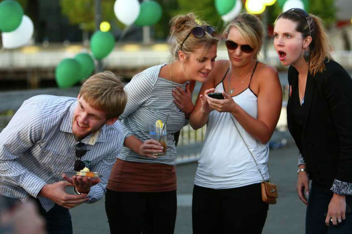 From left, Jesse Baumgartner, Kate Kuchin, Lindsey Grad and Katherine Mackinnon react to the first release of election results at the Let's Move Forward election night party on Tuesday, August 16, 2011 at Pier 57 on the Seattle waterfront. Initial results showed public support to continue with the replacement of the Alaskan Way Viaduct with a tunnel.