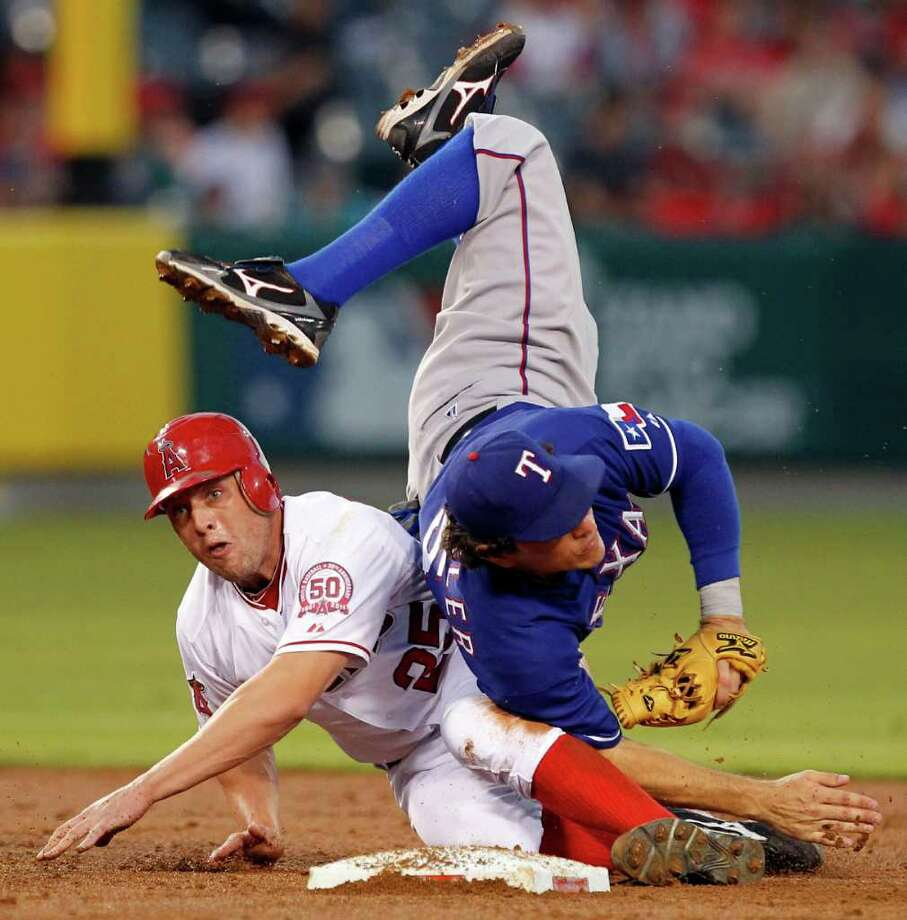 Los Angeles Angels' Peter Bourjos, left, upends Texas Rangers second baseman Ian Kinsler to break up a double play attempt during the second inning of a baseball game in Anaheim, Calif., Tuesday, Aug. 16, 2011. The Angels' Alberto Callaspo was safe at first. Photo: Alex Gallardo/Associated Press