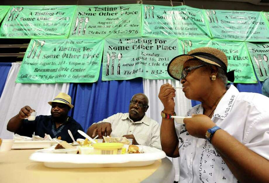 Brenda Green, (right) Olen Green and Ronald Chaison snack on samples of food collected during the Tasting for Some Other Place at the Beaumont Civic Center in Beaumont, Tuesday. Tammy McKinley/The Enterprise Photo: TAMMY MCKINLEY