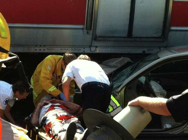 A 92-year-old man is taken into an ambulance after the car he was driving was struck by a Metro-North train in Darien, Conn. on Wednesday, August 17, 2011. Photo: John Nickerson