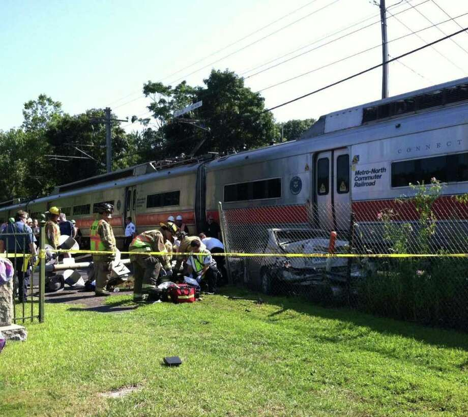 Emergency workers help the victim of a car/train crash in Darien Wednesday morning. Photo by Kristen Riolo. Photo: Contributed Photo