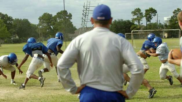 Spring football practice was held at the West Brook High School practice field Wednesday afternoon.  The team practiced many running plays with Head Coach Craig Stump, center, calling the plays and reacting to how well they were executed.   Dave Ryan/The Enterprise Photo: Tammy McKinley