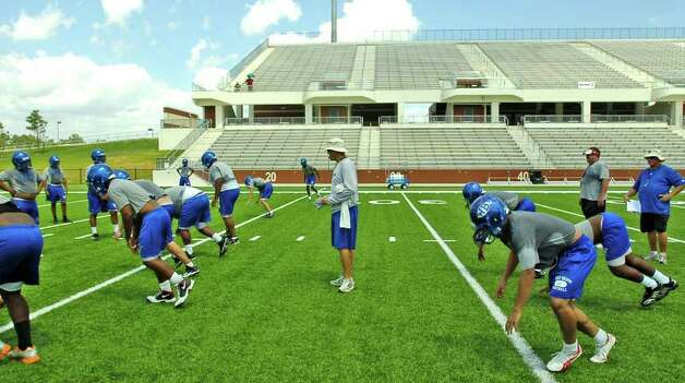 "Head Coach Craig Stump, center, watches his team go through warm up drills.    It was the first day of football practice and it was hot for the West Brook Bruin football team who reported for afternoon practice at the Carrol A. ""Butch"" Thomas Educational Support Center. Facilities at the high school are not ready yet.  Dave Ryan/The Enterprise"