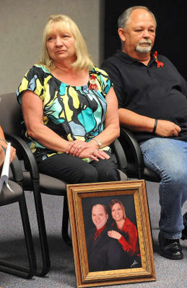Cynthia Hebert displays a portrait of her children, Bryan and Holly, at a news conference Monday. Photo: Guiseppe Barranco, The Beaumont Enterprise