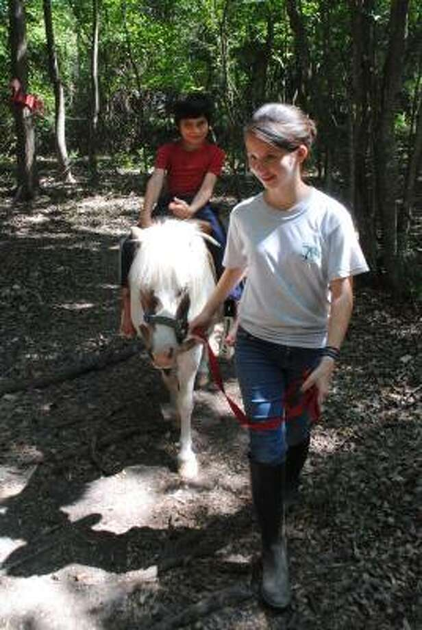 DAVE SCHAFER: FOR THE CHRONICLE MAKING A DIFFERENCE: Allyson Henry, 15, leads Big Cowboy, carrying Jorge Andres Cabrera, 7, through a trail at Halter Inc. The nonprofit uses miniature horses and other animals to help special-needs children. Photo: Dave Schafer:, For The Chronicle