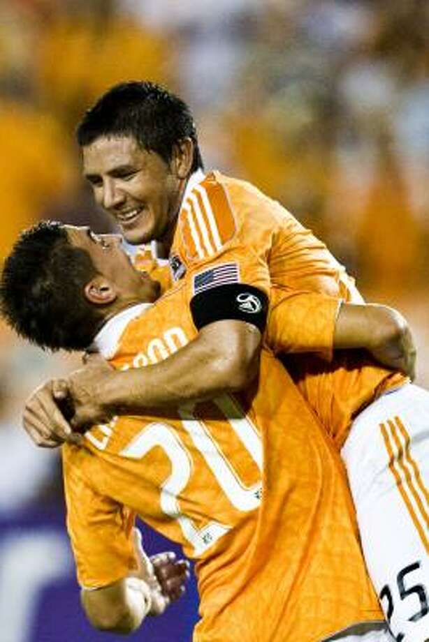 Dynamo forward Brian Ching (25) is hugged by teammate midfielder Geoff Cameron (20) after scoring a goal against the Seattle Sounders FC on Saturday night. Photo: Patrick T. Fallon, Chronicle