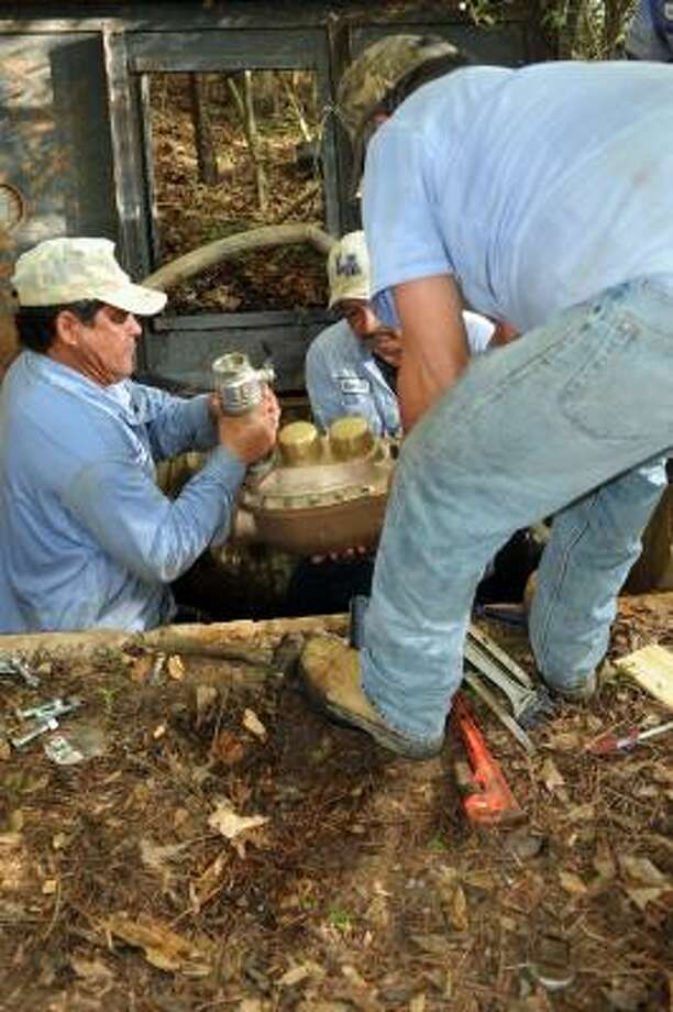JERRY BAKER: FOR THE CHRONICLE METER REPAIR: Juvensio Santillan, left, Ramiro Chavez and Antonio Rendon of The Woodlands Joint Powers Agency utility crew work the site of a faulty water meter at the Harvestwood Apartments. Photo: Jerry Baker, For The Chronicle