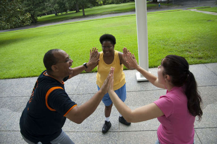 Stephen Findley, from left, Elanore Crystal Cornell and Lainie Diamond participate in a Laughter Yoga session last month in Menil Park. Photo: Prentice Danner