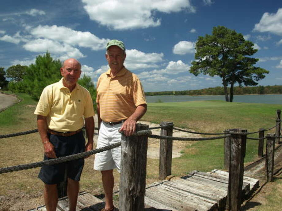 "Justin Curren, left, and Willie Wiginton, the current and immediate past president of the Waterwood Community Association, respectively, are spearheading the effort to return the Waterwood course to its old luster. They're standing beside the course's signature hole - the par-3 14th -  that is known as ""The Cliffs"" and runs alongside Lake Livingston. Photo: Mike Bailey, For The Chronicle"