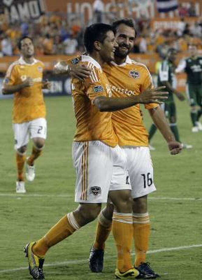 Brian Ching, center, and Adam Moffat, right, scored the Dynamo's two goals in Sunday night's victory. Photo: Cody Duty, Chronicle