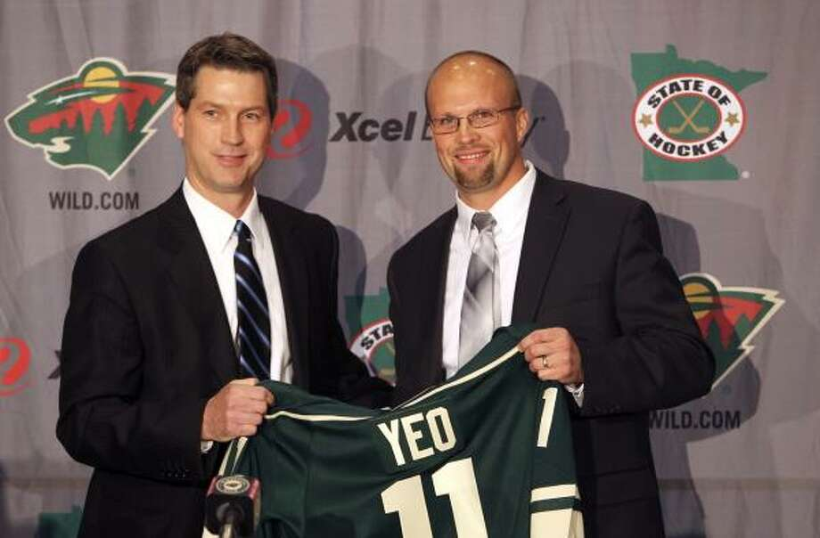 New Minnesota Wild head coach Mike Yeo, right, holds up a jersey with general manager Chuck Fletcher. Photo: David Joles, Associated Press