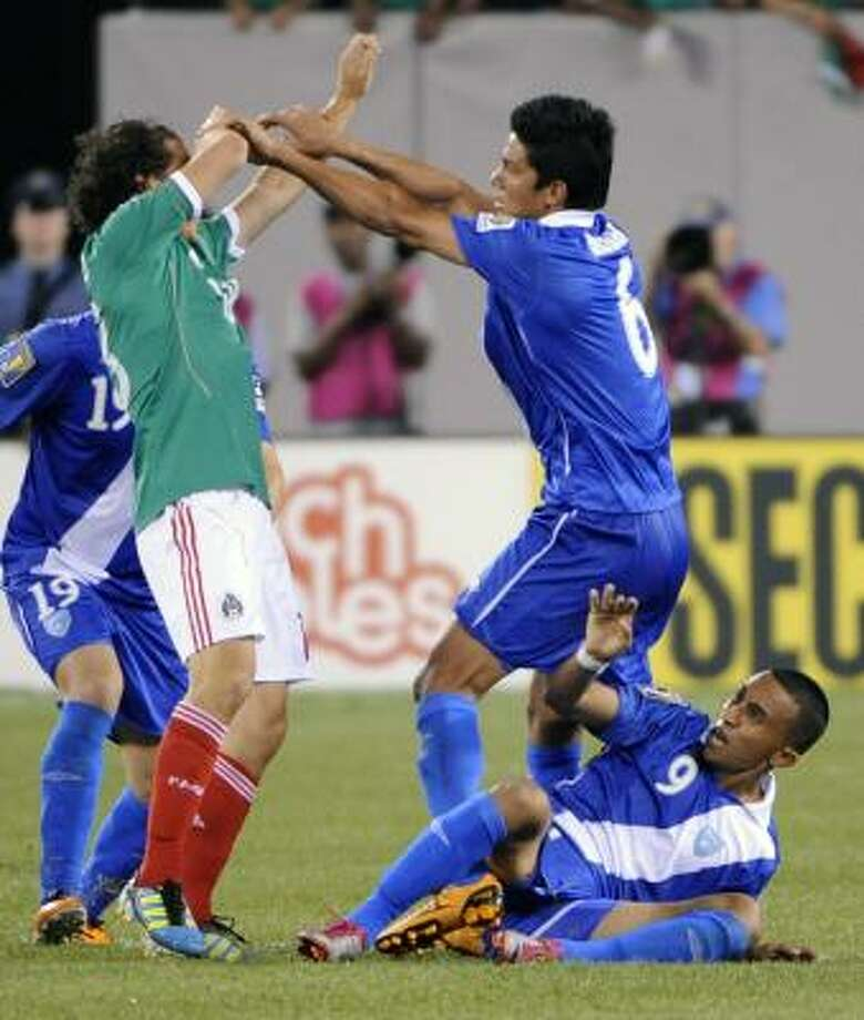 Guatemala's Gustavo Cabrera, top right, and Mexico's Andres Guardado spar as Guatemala's Wilfred Velasquez tries to keep clear as tempers flare in their Gold Cup match Saturday. Photo: Bill Kostroun, Associated Press