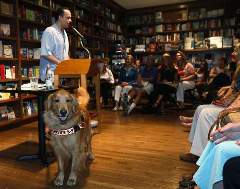 Montalvàn speaks as his service dog, Tuesday, stands at the ready in Coral Gables, Fla. Photo: Wilfredo Lee, Associated Press