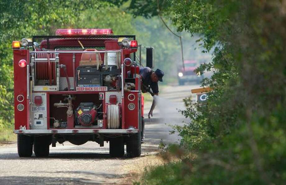 A volunteer firefighter hoses off his arm Monday while extinguishing flare-ups south of Stoneham along County Road 304 in Grimes County. Stoneham is west of Plantersville. Photo: Mayra Beltran, Chronicle